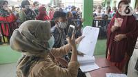 Petugas PT Pos Indonesia memotret wajah penerima Bantuan Sosial Tunai (BST) bulan Januari di halaman Masjid Jami Al-Hidayah RW 01 Bedahan, Depok, Selasa (16/2/2021). Sekitar 159.470 Keluarga Penerima Manfaat (KPM) di Kota Depok menerima BST yang disalurkan pada Februari ini (merdeka.com/Arie Basuki)