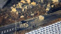 Sebuah batu besar tergeletak di jalan setelah gempa bumi melanda kota, di Soma, prefektur Fukushima, timur laut Jepang, Minggu (14/2/2021).  Sejauh ini belum ada peringatan tsunami. (Hironori Asakawa/Kyodo News via AP)