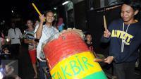 Warga memukul bedug sambil mengumandangkan takbir di kawasan tanah abang, Jakarta,Selasa (5/7). Bagi Umat Muslim Indonesia mengumandangkan Takbir ialah sebagai suatu tanda menyambut hari Raya Idul Fitri 1437 Hijriah. (Liputan6.com/Helmi Afandi)