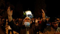 Muslim Palestina berdoa di kompleks masjid al-Aqsa, situs paling suci ketiga bagi umat Islam, di Yerusalem, Minggu (31/5/2020). Kompleks masjid Al-Aqsa resmi kembali dibuka hari ini, Minggu (31/5) setelah ditutup dua bulan sebagai bagian upaya memutus penularan virus corona. (Ahmad GHARABLI/AFP)