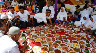 Orang-orang menikmati makan siang selama perayaan maulid akbar Nabi Muhammad SAW di Banda Aceh, Aceh, Kamis (6/2/2020). Acara maulid akbar tersebut menyediakan 808 hidangan dari 90 desa dan instansi pemerintah dengan mengundang 25.000 tamu dari berbagai daerah. (Photo by Chaideer MAHYUDDIN / AFP)
