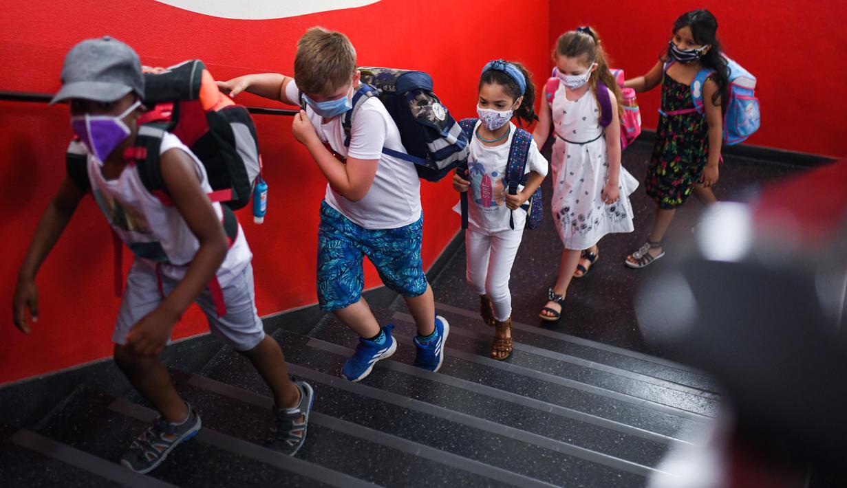 Siswa dengan masker menaiki tangga menuju ruang kelas mereka di sekolah dasar Petri di Dortmund, Jerman, Rabu (12/8/2020). Para siswa di negara bagian Jerman, North Rhine-Westphalia, harus mengenakan masker setiap waktu ketika mereka kembali ke sekolah pada Rabu ini. (Ina FASSBENDER/AFP)