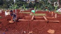 Pekerja menyiapkan makam jenazah terduga terinfeksi COVID-19 di TPU Pondok Ranggon, Jakarta, Jumat (8/5/2020). Lahan khusus pemakaman korban COVID-19 yang berlokasi di blok AA-1 sudah penuh sehingga pemakaman jenazah baru dilakukan di lahan sekitar BLAD 115. (Liputan6.com/Helmi Fithriansyah)
