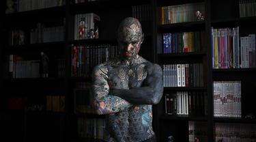 Sylvain Helaine, yang juga dikenal sebagai Freaky Hoody, berpose selama sesi pemotretan di Palaiseau, Paris, Prancis (22/9/2020). Berprofesi sebagai guru sekolah dasar tak menghalangi pria 35 tahun untuk gemar menghiasi tubuhnya dengan tato. (AFP/Christophe Archambault)