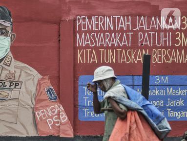 Pejalan kaki melintasi mural bertemakan Imbauan Protokol Kesehatan Covid-19 di kawasan Bukit Duri, Jakarta, Minggu (25/10/2020). Gubernur DKI Anies Baswedan kembali memperpanjang Pembatasan Sosial Berskala Besar (PSBB) masa transisi hingga 8 November 2020. (merdeka.com/Iqbal Nugroho)