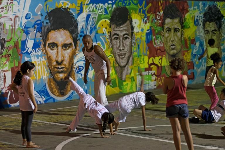 Seorang pelatih sedang memperhatikan anak didiknya melakukan gerakan Capoeira di dekat tembok lukisan wajah pemain top dunia, Brasil, Rabu (21/05/2014) (AFP PHOTO/Yasuyoshi CHIBA).