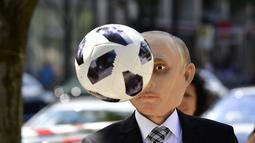 Seorang aktivis Reporters Without Borders mengenakan topeng Presiden Rusia Vladimir Putin selama protes di depan kedutaan Rusia menjelang dimulainya Piala Dunia Sepak Bola 2018 di Berlin, Jerman (12/6). (AFP Photo/Tobias Schwarz)