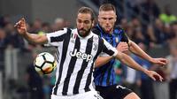 Striker Juventus, Gonzalo Higuain, berebut bola dengan bek Inter Milan, Milan Skriniar, pada laga Serie A di Stadion Giuseppe Meazza, Sabtu (28/4/2018). Inter Milan takluk 2-3 dari Juventus. (AP/Matteo Bazzi)