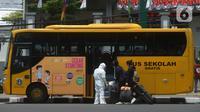 Bus sekolah menjemput pasien Covid-19 berstatus orang tanpa gejala (OTG) di Puskesmas Jatinegara, Jakarta, Selasa (22/9/2020). Sejumlah unit bus sekolah kini dialihfungsikan menjadi kendaraan untuk mengantar pasien Covid-19 berstatus OTG menuju RS Darurat Wisma Atlet. (merdeka.com/Imam Buhori)