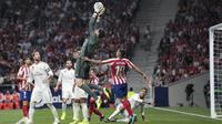 Kiper Real Madrid, Thibaut Courtois berusaha menangkap bola saat bertanding melawan Atletico Madrid pada lanjutan La Liga di stadion Wanda Metropolitano, Spanyol (28/9/2019). Madrid dan Atletico bermain imbang 0-0. (AP Photo/Bernat Armangue)