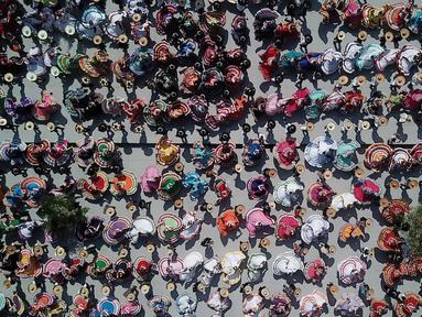 Pandangan udara pasangan menari mengikuti irama musik mariachi untuk memecahkan Rekor Dunia Guinness di Guadalajara, Meksiko, 24 Agustus 2019. Sebanyak 882 orang menari dengan kostum tradisional dalam upaya memecahkan rekor dunia untuk kategori tarian rakyat terbesar. (ULISES RUIZ/AFP)