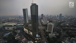 Suasana gedung bertingkat yang terlihat samar karena kabut polusi di Jakarta, Selasa (9/7/2019). Berdasarkan data DLH DKI Jakarta penyebab polusi di Jakarta semakin buruk akibat emisi kendaraan bermotor yang mencapai 75 persen, ditambah pencemaran dari industri dan limbah. (Liputan6.com/Johan Tallo)