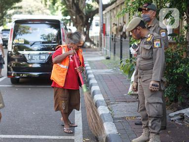 Petugas Satpol PP memberikan sanksi menyapu kepada warga yang tidak menggunakan masker di kawasan Pasar Baru, Jakarta, Jumat (21/8/2020). Sanksi tersebut dilakukan sebagai bagian dari upaya pencehagan penyebaran virus covid-19. (Liputan6.com/Immanuel Antonius)