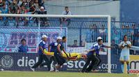 Kiper Persela Lamongan Choirul Huda dibawa oleh tim medis usai mengalami benturan dengan rekan setim, Ramon Rodrigues saat pertandingan Liga 1 di stadion Surajaya, Lamongan (15/10). (AFP Photo/Juni Kriswanto)