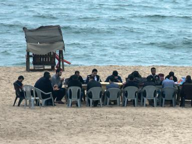 Warga Palestina berkumpul untuk berbagi makanan buka puasa selama bulan suci Ramadan, saat pandemi virus corona, di sepanjang pantai kota Gaza pada 13 Mei 2020. Mereka menunggu waktu berbuka puasa sambil menyaksikan matahari terbenam. (Photo by MAHMUD HAMS / AFP)