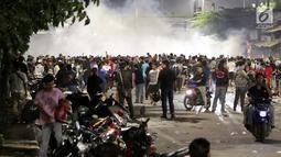 Massa berkumpul saat terjadi ricuh akibat unjuk rasa di sekitar jalan Pejompongan, Jakarta, Rabu (25/9/2019). Polisi menembakan gas air mata di kerumunan massa setelah unjuk rasa pelajar STM bentrok dengan aparat kepolisian dibelakang Gedung DPR/MPR. (Liputan6.com/Helmi Fithriansyah)