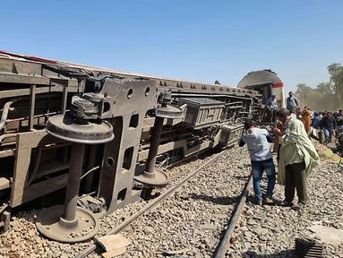 Orang-orang berkumpul di sekitar reruntuhan dua kereta yang bertabrakan di distrik Tahta di provinsi Sohag, sekitar 460 km (285 mil) selatan ibu kota Mesir, Kairo (26/3/2021). Dilaporkan tabrakan ini menewaskan sedikitnya 32 orang dan melukai banyak lainnya. (AFP)