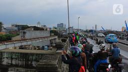 Sejumlah pengendara menepi untuk melihat kondisi kali Ciliwung dan beberapa anak melakukan aksi lompat dari atas jembatan Ciliwung Kalibata, Jakarta, Selasa (25/2/2020). (merdeka.com/magang/Muhammad Fayyadh)