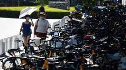 Dua orang wanita berjalan melintasi sepeda-sepeda yang diparkir memenuhi trotoar di Beijing, China (21/7/2020).  Seperti diketahui Beijing telah menerapkan bike sharing yang sudah tersedia di trotoar-trotoar Kota Beijing. (AFP Photo/Greg Baker)