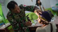 Tim medis dari satuan tugas militer Indonesia memeriksa seorang pasien di rumah sakit setempat di Agats, Asmat, provinsi Papua Barat (26/1). (AFP/Bay Ismoyo)