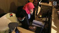 Penyidik KPK berbincang dengan salah seorang pegawai saat menggeledah Kantor Pusat PLN, Jakarta, Senin (16/7). Penggeledahan diduga merupakan rangkaian dari penyelidikan kasus suap proyek PLTU Riau-1. (Liputan6.com/Arya Manggala)