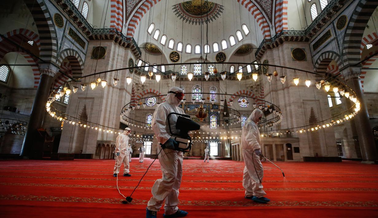 Pekerja mengenakan pakaian pelindung menyemprotkan disinfektan bagian dalam Masjid Suleymaniye yang bersejarah pada hari ketiga Idul Fitri di Istanbul, Selasa (26/5/2020). Beberapa masjid didisinfektan sebelum dibuka kembali pada 29 Mei usai ditutup selama lebih dari enam minggu. (AP/Emrah Gurel)