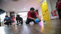 """Riza Fanani dari tim Social Media beraksi dalam lomba """"Blow Your Cup"""" di acara Agustusan di di Gedung KLY, Gondangdia, Jakarta, Jumat (16/8). (Liputan6.com/Faisal Fanani)"""
