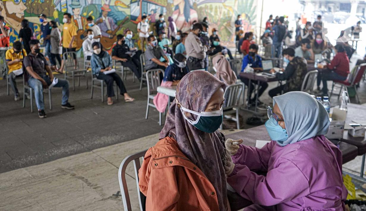 Warga menerima vaksinasi COVID-19 Sinovac di Terowongan Kendal, Jakarta Pusat, Jumat (30/7/2021). Sebanyak 600 dosis disiapkan untuk masyarakat pengguna transportasi publik di kawasan integrasi Commuter Line, kereta bandara, dan Transjakarta tersebut. (Liputan6.com/Faizal Fanani)