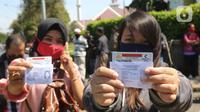 Warga mengurus Surat Izin Mengemudi (SIM) di mobil layanan SIM Keliling Masjid At-Tin, Jakarta Timur, Kamis (4/6/2020). Direktorat Lalu Lintas Polda Metro Jaya mengoperasikan kembali layanan mobil SIM Keliling untuk mengantisipasi antrean pemohon. (Liputan6.com/Herman Zakharia)