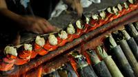Pekerja mengambil lemang bambu di sentra pembuatan lemang kawasan Kramat Raya, Senen, Jakarta, Jumat (17/6). Pembuatan lemang pada Ramadan meningkat lebih dari 300 persen dibanding hari biasa hingga mencapai 500 buah per-hari (Liputan6.com/Gempur M Surya)