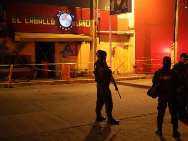 Polisi menjaga klub penari telanjang yang menjadi lokasi penyerangan di Coatzacoalcos, Veracruz, Meksiko, Rabu (28/8/2019). Sebanyak 25 orang tewas dan 11 lainnya luka-luka setelah serangan kelompok bersenjata di sebuah klub penari telanjang bernama Caballo Blanco. (AP Photo/Felix Marquez)