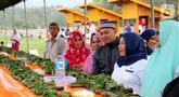 Warga melihat bungkus nasi kuning selama Gebyar Safar 1441 H di Desa Pangi, Kecamatan Suwawa Timur, Kabupaten Bone Bolango (Bonebol), Rabu (23/10/2019). Sebanyak 5.000 bungkus nasi kuning disajikan dalam perayaan yang turut dihadiri Bupati Bone Bolango, Hamim Pou, itu. (Liputan6.com/Arfandi Ibrahim)