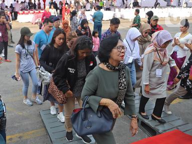 Anggota keluarga korban jatuhnya pesawat Lion Air JT 610 menaiki kapal KRI Semarang 594 di Dermaga JICT 2 Tanjung Priok, Jakarta, Selasa (29/10/2019). Mengenang setahun jatuhnya pesawat rute Jakarta-Pangkal Pinang itu, mereka melakukan tabur bunga di perairan Karawang. (Liputan6.com/Herman Zakharia)