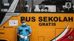 Petugas berjaga di depan bus sekolah yang terparkir di Kawasan Stasiun Sudirman, Jakarta, Jumat (19/6/2020). Dishub DKI Jakarta telah mengerahkan 50 armada bus sekolah untuk membantu mengurai lonjakan penumpang KRL. (Liputan6.com/Faizal Fanani)