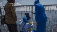 Keluarga awak KRI Nanggala 402 menghadiri Upacara Tabur Bunga Tabur Bunga dari geladak Helly KRI Dr Soeharso-990 di perairan utara pulau Bali, Jumat (30/4/2021). Kegiatan yang diikuti dari 53 keluarga awak KRI Nanggala 402 yang tenggelam itu diwarnai suasana haru dan kesedihan. (Juni Kriswanto/AFP)