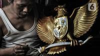 Perajin menyelesaikan proses pewarnaan patung Garuda Pancasila di Jalan Bali Raya, Jakarta, Kamis (1/10/2020). Dampak Covid-19 menyebabkan produksi patung lambang negara Republik Indonesia tersebut menurun dan sempat tutup selama 3 bulan pada masa awal pandemi. (merdeka.com/Iqbal S. Nugroho)