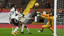 Kiper Liverpool, Alisson Becker melakukan penyelamatan dalam laga lanjutan Liga Inggris 2020/21 pekan ke-12 melawan Fulham di Craven Cottage, Minggu (13/12/2020). Liverpool bermain imbang 1-1 dengan Fulham. (AFP/Mike Hewitt/Pool)