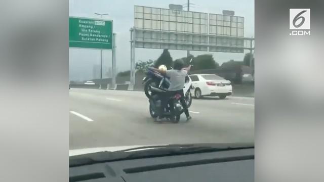 Seorang pengendara motor nekat membonceng seorang penumpang dan juga sebuah motor di jalanan ramai.