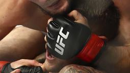 Khabib Nurmagomedov saat mengunci Dustin Poirier dalam pertarungan UFC 242 di Mal Yas di Abu Dhabi, Uni Emirat Arab (7/9/2019). Kemenangan atas Dustin sudah diprediksi oleh kebangakan orang. (AP Photo/ Mahmoud Khaled)