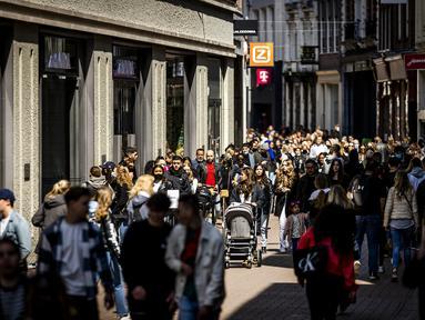 Pelanggan berjalan di Kalverstraat shopping street saat toko-toko diizinkan menerima pelanggan tanpa membuat janji di Amsterdam, Rabu (28/4/2021). Belanda melonggarkan pembatasan ketat terkait Covid-19, mengakhiri jam malam dan mengizinkan kafe untuk buka di luar ruangan. (REMKO DE WAAL/ANP/AFP)