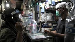 Pedagang alat pelindung wajah atau face shield melayani pembeli di salah satu kios Pasar Pramuka, Jakarta, Rabu (3/6/2020). Face shield di Pasar Pramuka dijual dengan harga mulai Rp 15 ribu hingga Rp 90 ribu per unit. (merdeka.com/Iqbal S. Nugroho)