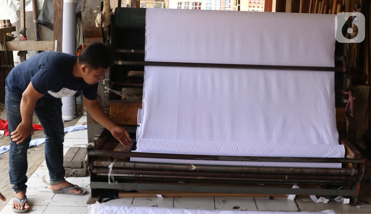 Pedagang merapikan bahan kain yang akan dijual di kawasan Tangerang, Banten, Sabtu (25/9/2021). Kementerian Perindustrian memberikan stimulus bagi industri tekstil dalam negeri berupa program Restrukturisasi Mesin/Peralatan Industri Penyempurnaan dan Percetakan Kain. (Liputan6.com/Angga Yuniar)