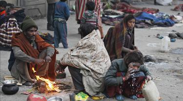 Seorang tunawisma mencuci wajahnya saat yang lain menghangatkan diri mereka dengan api unggun di bawah jembatan layang di Jammu, India, Sabtu (28/12/2019). Sekitar 800 juta orang di India hidup dalam kemiskinan. (AP Photo/Channi Anand)