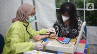 Petugas medis mengukur tekanan darah ke dokter di Puskesmas Cengkareng, Jakarta Barat, Selasa (9/2/2021). Vaksinasi Sinovac yang dilakukan secara paralel untuk tenaga kesehatan di atas 60 tahun dilakukan karena mereka rentan tertular virus Covid-19. (Liputan6.com/Fery Pradolo)