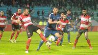 Striker Madura United, Aleksandar Rakic membuang bola dari kejaran bek PSIS Semarang, Wallace Costa Stadion Moch Soebroto, Magelang, Selasa (17/12/2019). (Bola.com/Vincentius Atmaja)