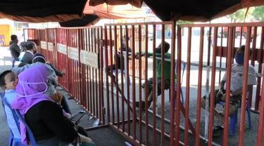 Keluarga yang menengok peserta karantina di GOR Satria, Banyumas, dibatasi jeruji besi. (Foto: Liputan6.com/Humas Pemkab Banyumas)