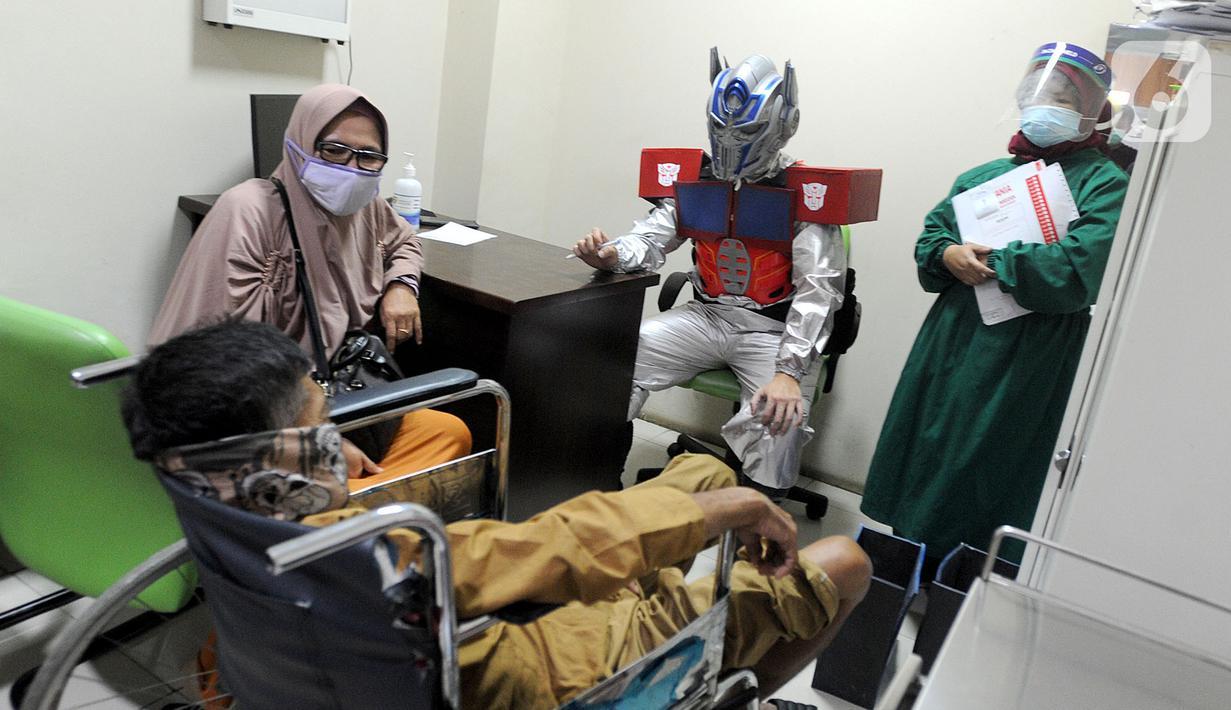 Dokter Rollando Erric Manibuy SpOT mengenakan alat pelindung diri (APD) ala transformer saat melayani pasiennya di RS Vania, Bogor, Jawa Barat, Jumat (22/5/2020). Penggunaan APD unik sejak merebaknya COVID-19 tersebut agar pasien tetap optimis meski sedang dalam pandemi. (merdeka.com/Arie Basuki)