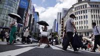Orang-orang yang memakai masker untuk melindungi dari penyebaran virus corona berjalan di bawah terik matahari di distrik Perbelanjaan Ginza di Tokyo, Selasa (10/8/2021). (AP Photo/Eugene Hoshiko)