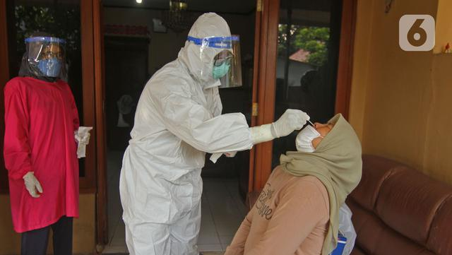 Warga melakukan tes usap PCR Covid-19 di Jalan As-Syafiiyah, Cipayung, Jakarta Timur, Jumat (21/5/2021). Kawasan tersebut memberlakukan mikro lockdown serta tes usap PCR secara massal. (Liputan6.com/Herman Zakharia)