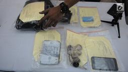 Petugas merapikan barang bukti saat rilis pengungkapan kasus penjambretan di Polda Metro Jaya, Jakarta, Senin (8/4). Penjambretan itu terjadi pada Jumat (5/4) pukul 02.00 WIB. (Liputan6.com/Herman Zakharia)